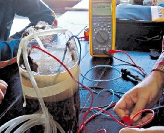 A orillas del Río de la Plata, estudiantes porteños de tres escuelas técnicas buscan barro para volcar en un recipiente, luego le agregan agua y con dos minas de lápiz negro conectadas por un cable eléctrico logran producir energía para abastecer una calculadora o un pequeño motor.