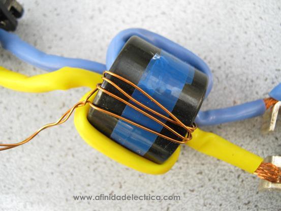 En la siguiente imagen se observa un detalle del núcleo toroidal con las bobinas de corriente de fase y neutro (amarillo y celeste) y la de corriente diferencial o residual (alambre de cobre esmaltado).