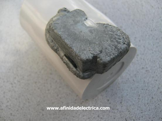 El capacitor presenta una deformación con erupción de material sobre el recipiente plástico de envoltura. Esto podría ser causado por la combustión interna del material dieléctrico por un cortocircuito.