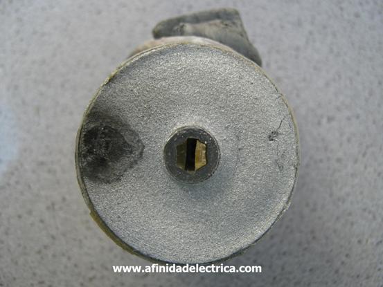 En el centro observamos el carrete cilíndrico sobre el que se enrolla el film para darle forma al capacitor y que, además posee una ranura rectangular utilizada para encastrar el anclaje mecánico de los terminales.