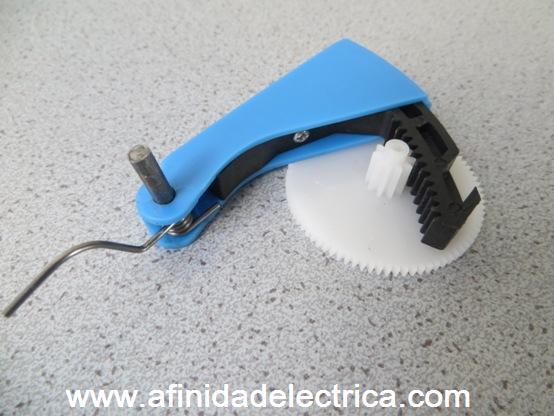 La palanca de accionamiento es una manija en forma de L que en uno de sus extremos tiene una cremallera dentada que transmite el movimiento de la mano al engranaje blanco.