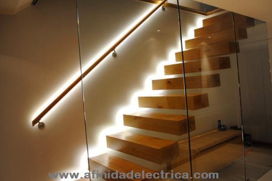 Para señalizar e iluminar esta escalera, se han instalado tiras de LEDs encapsuladas en los bordes de los escalones y ocultas detrás del pasamanos.