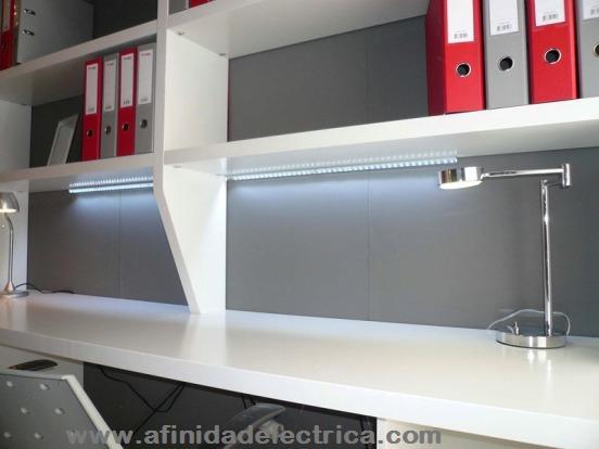 En la siguiente imagen se observa la instalación de tiras de LEDs de color blanco frío adheridas debajo un estante que proporcionan iluminación directa sobre el escritorio.